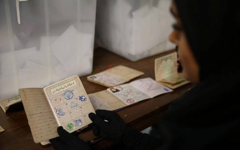 An electoral employee checks a document before closing vote for the presidential election in a polling station in Tehran, Iran, May 19, 2017. TIMA via REUTERS