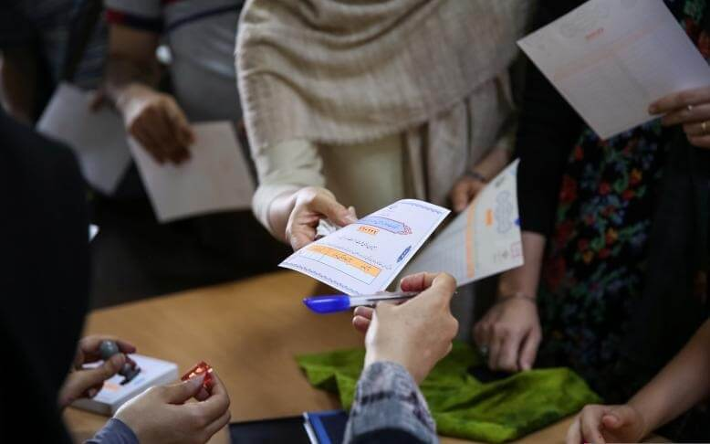 Voters receive ballot papers during the presidential election in a Jewish and Christian district in the centre of Tehran, Iran, May 19, 2017. TIMA/via REUTERS