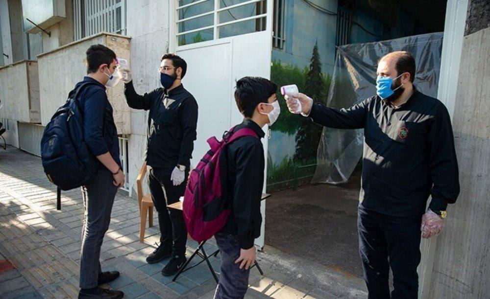 コロナ流行当初のテヘラン市内のある男子中学校の登校時の様子。校舎に入る前に生徒1人1人を検温